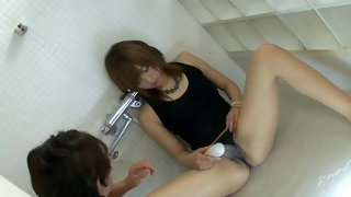 Naughty Asian girl uses shower handle to tease her pussy