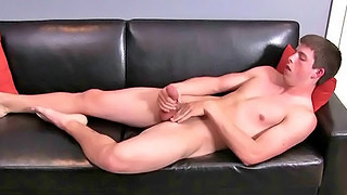 Attractive gay dude strips on the sofa and wanks his hard dong