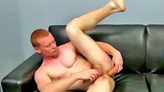 Cute ginger gay dude toys his ass on the black sofa