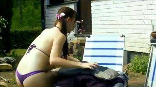 Fetching shemale babe enjoys tanning in a bikini